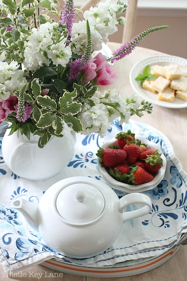Floral tray holding a teapot, strawberries and a flower arrangement.