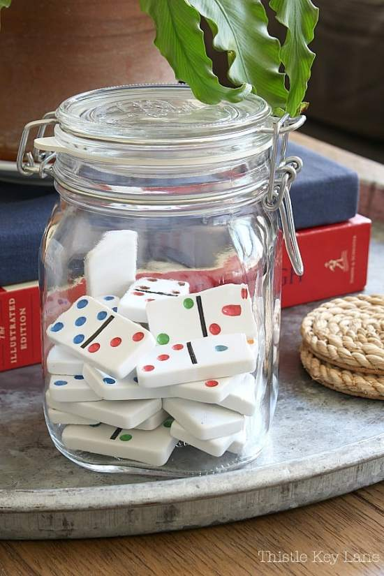 A glass jar holds colorful dominoes.