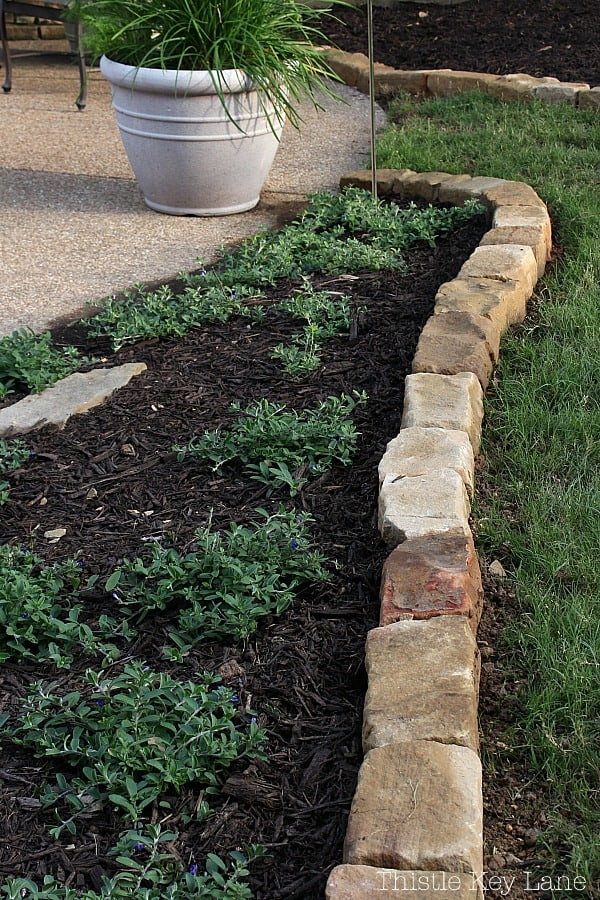 Summer ready patio and garden tour with rock borders around flower beds.