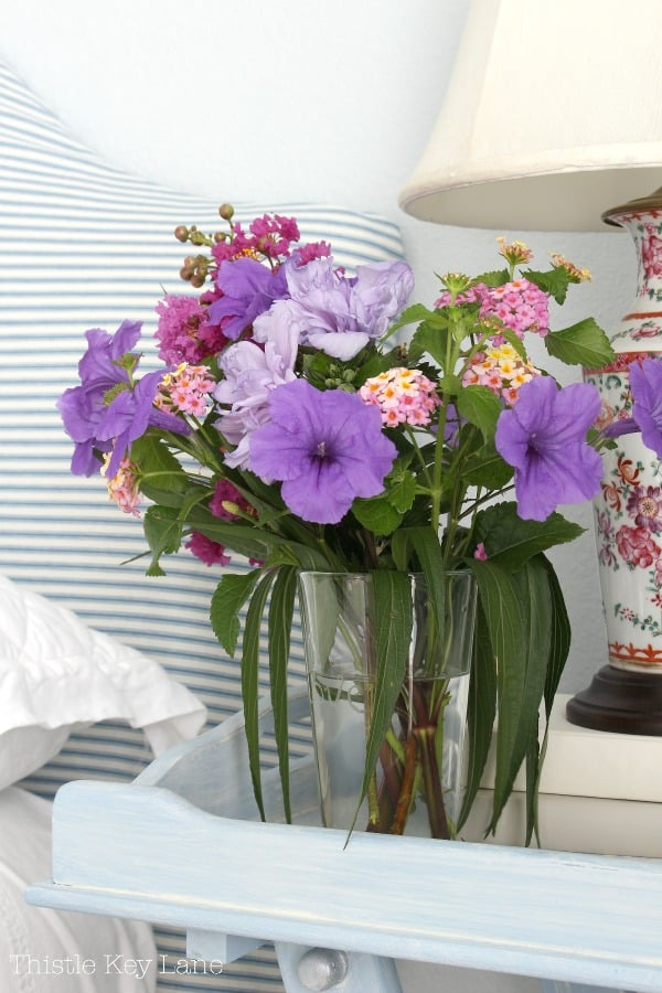 Purple and pink garden flowers on the bedside table.
