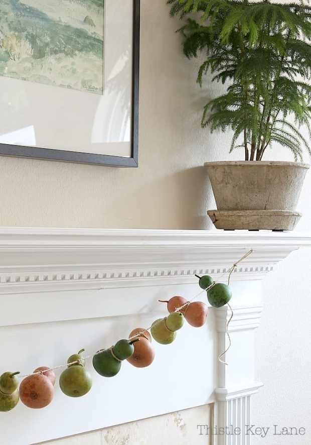 Whimsical summer to fall mantel and a gourd garland.