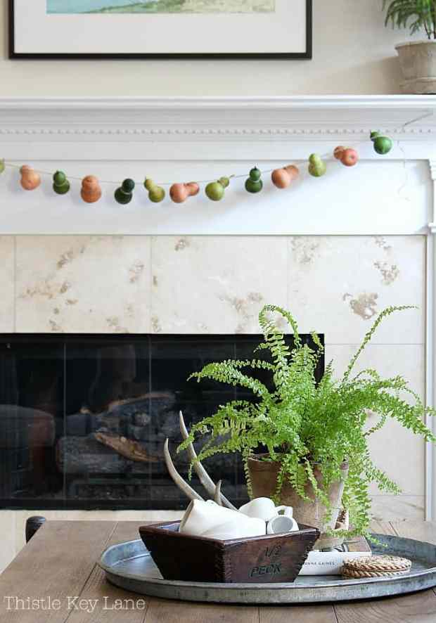 Transitional summer to fall mantel and a gourd garland.