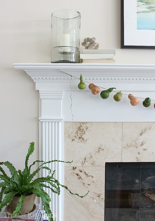 Summer to fall mantel and a gourd garland with neutral colors.