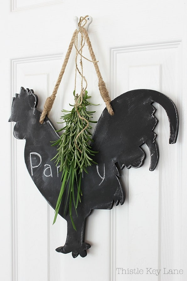 Rooster blackboard with hanging herbs.