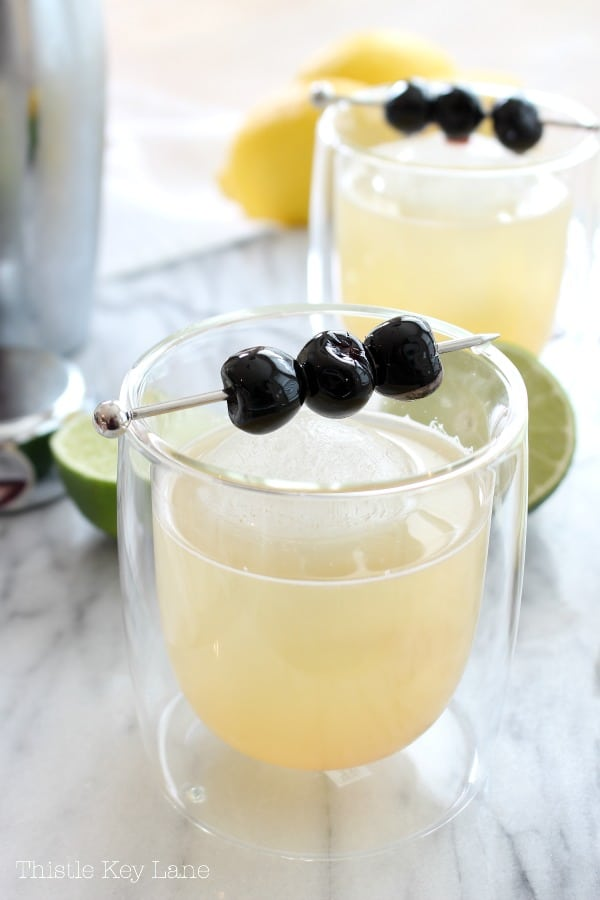 Classic whiskey sour cocktail recipe garnish with cherries.
