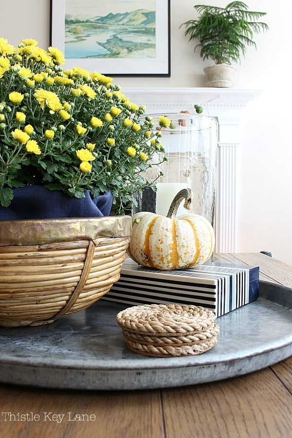 Decorating with yellow mums and a tiger pumpkin on a metal tray.