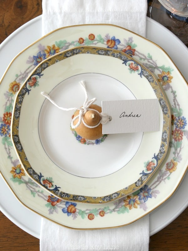 Place setting flat lay with autumn colors and a gourd place card.