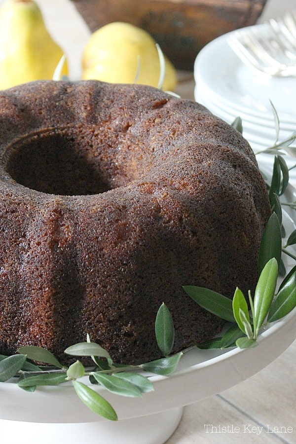 Rich and moist bundt cake on a white cake stand garnished with leaves.