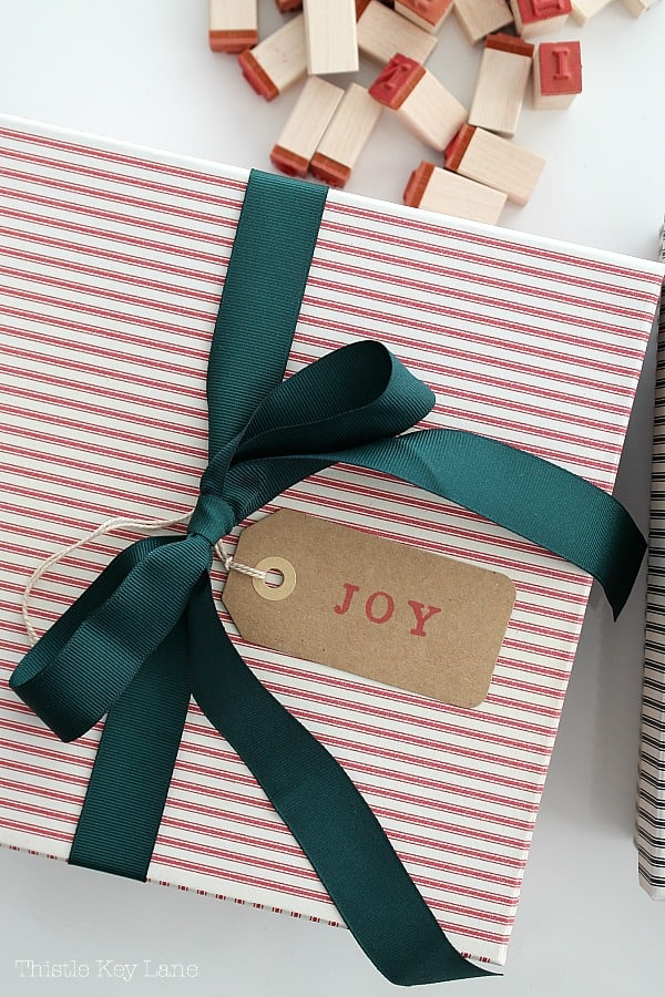 Black ticking stripe box with green ribbon and Joy gift tag.