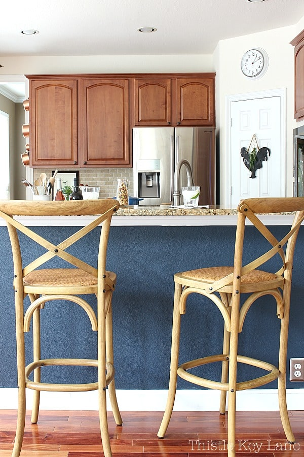 Barstools with navy wall and kitchen in the background.