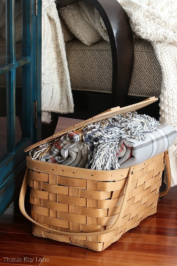 Winter Decorating Family Room Tour - Picnic basket holding plaid throws.