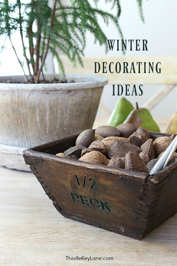 Winter Decorating Family Room Tour - wood box holding nuts with plant and pears in background.