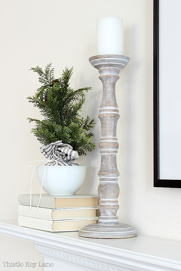 Evergreen topiary with fabric wrapped base in a white bowl and a tall candlestick on the mantel.