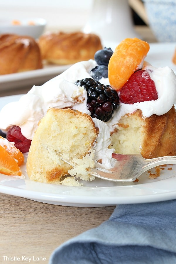 Pound cake with whipped cream, berries and orange slices.