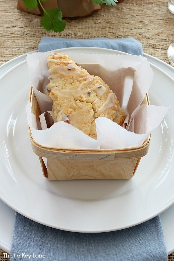 Lavender and honey scones in a berry basket on white plates.