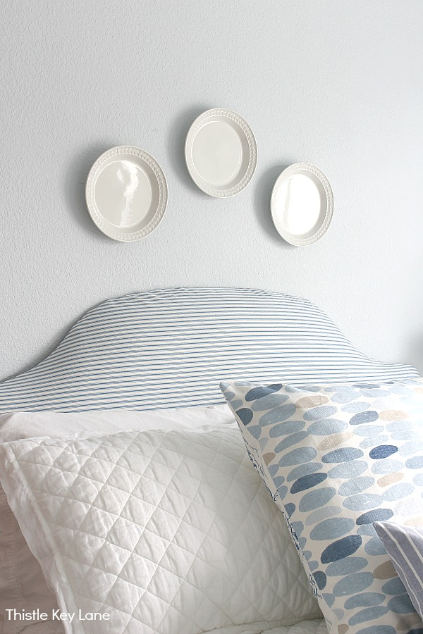 White plates hanging on light blue wall with ticking headboard.