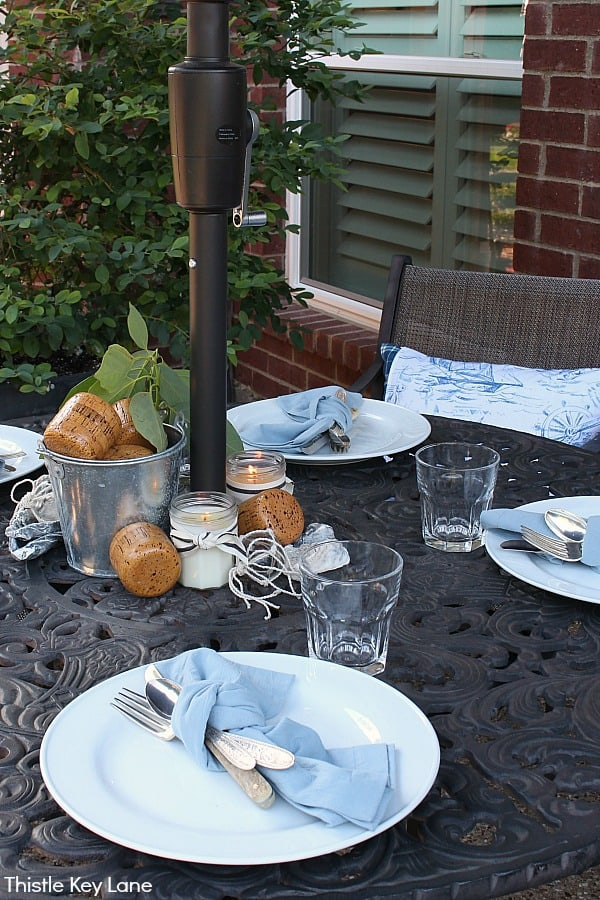 Patio tablescape with white plates and accents of blue.