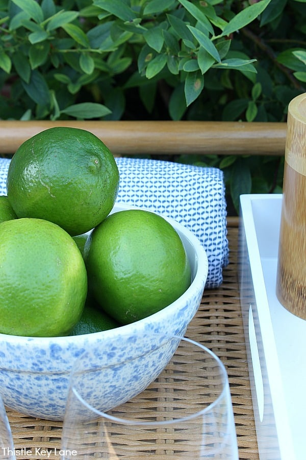 Blue speckled bowl with limes on a rattan cart with blue and white kitchen towel.