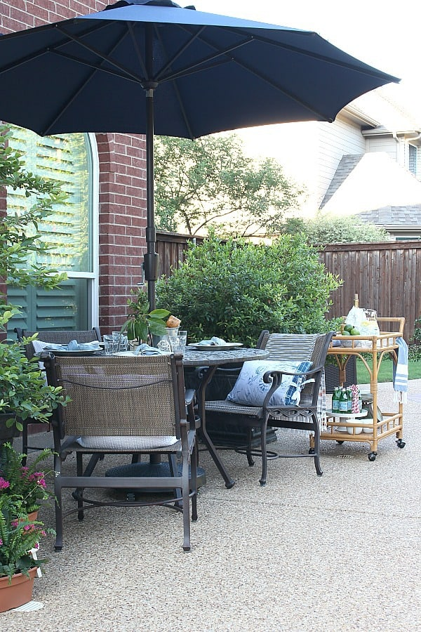 Relaxing Patio Style With Blue And White Accents -Patio table and chairs with green plants and a bar cart.