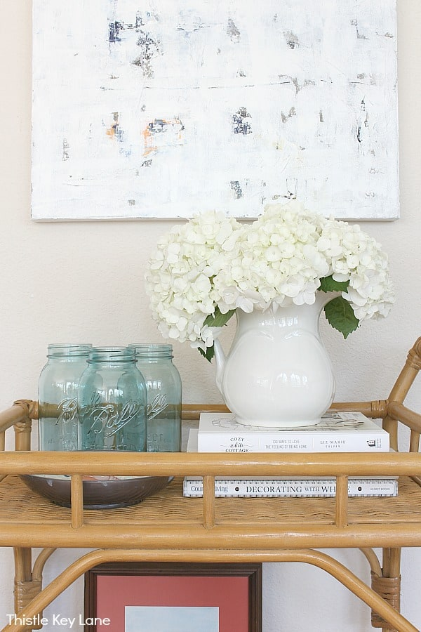 Blue jars, hydrangea blooms in a ironstone pitcher sitting on top of books.