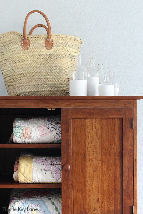 Armoire with quilts, French basket and white vases. How To Create Vases With Chalk Paint.