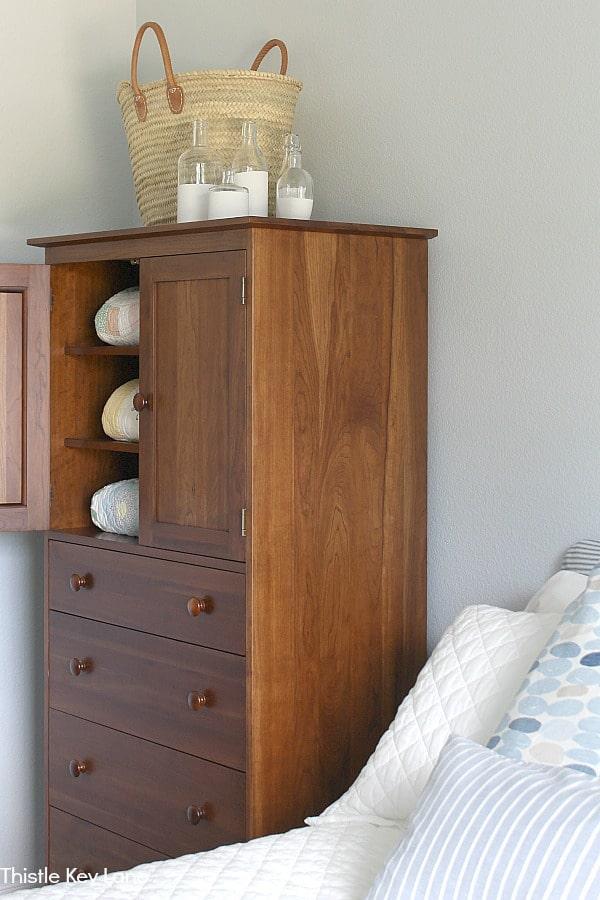 Bedroom armoire with door open. Basket and vases on top.