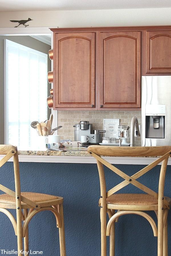 View of bar stools and wood kitchen cabinets.