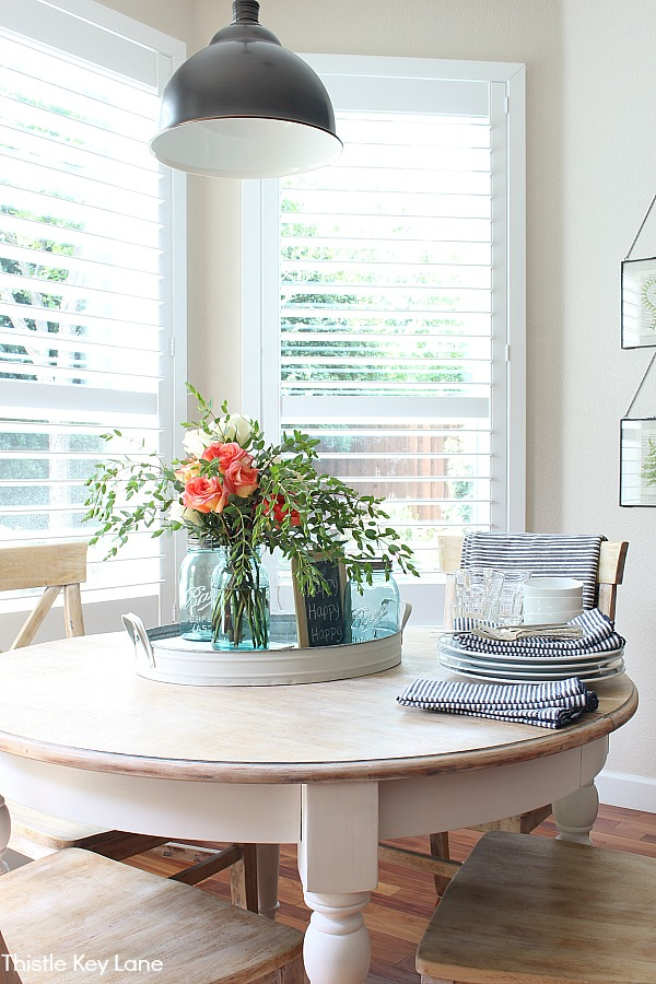 Breakfast table with white dishes and a rose centerpiece. -Simple Summer Home Decorating Tour.