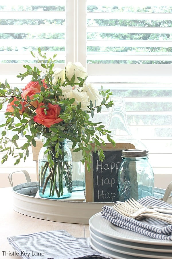 Coral and white roses with blue jars.