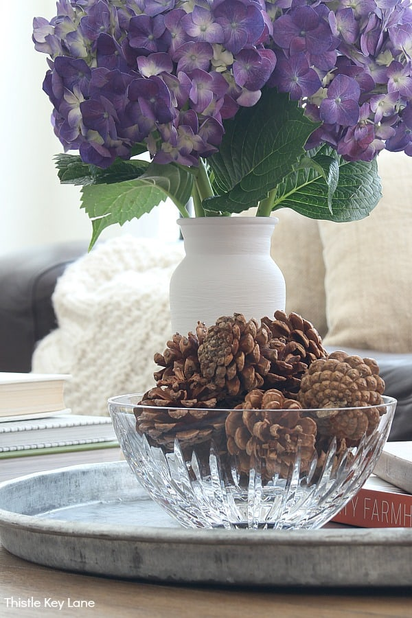 Pinecones in a glass bowl with purple hydrangeas in a white vase.
