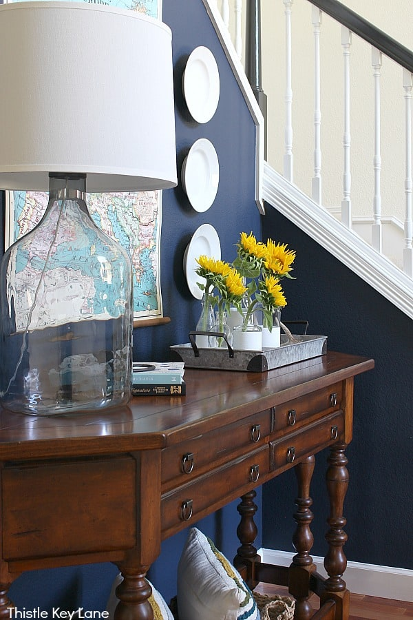 Side view of table with large lamp and navy wall -Summer To Fall Entry Table With Sunflowers.