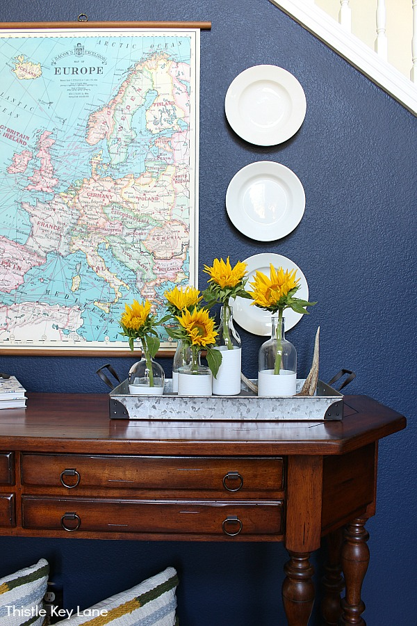 White ironstone plates and map on navy wall - Summer To Fall Entry Table With Sunflowers.