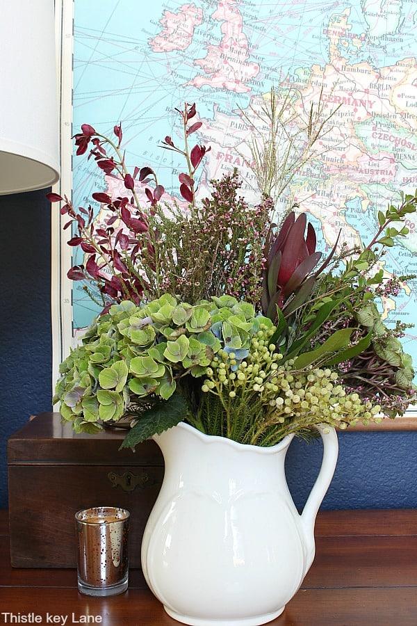 Green hydrangea arrangement in a white ironstone pitcher.