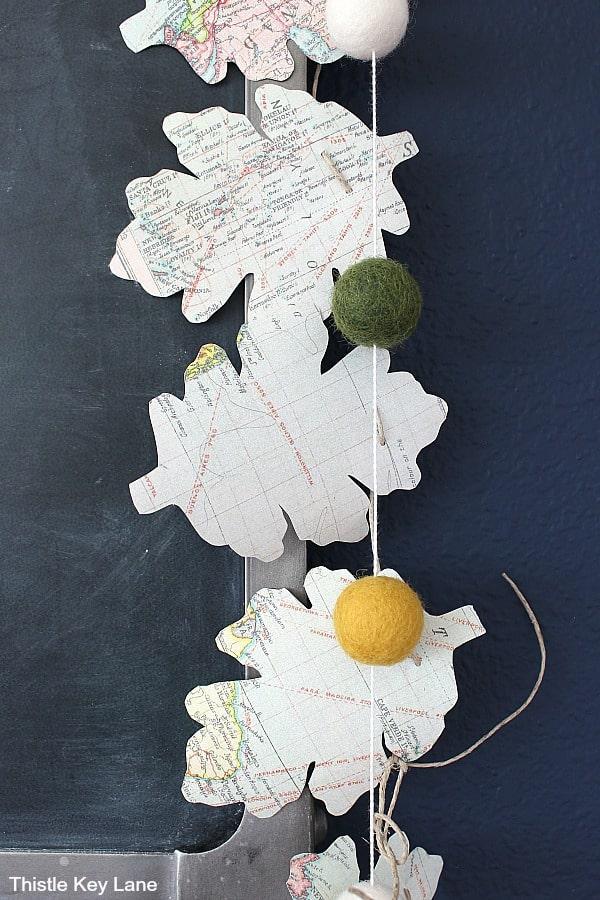 Leaf garland and wool felt pompoms on chalkboard. DIY Map Leaf Garland And Fall Printables.