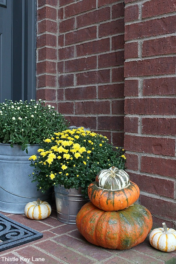 Stair stepping mums and pumpkins on a small porch. Fall Decorating Ideas For A Small Porch.