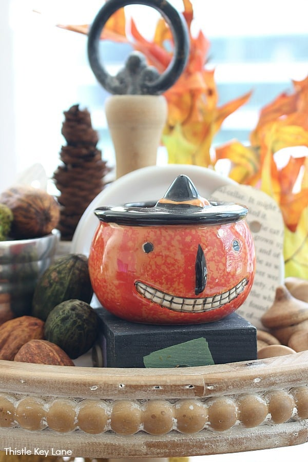 Grinning Pumpkin Candle, Wood Acorns, Green And Brown Pecans, White Dishes.
