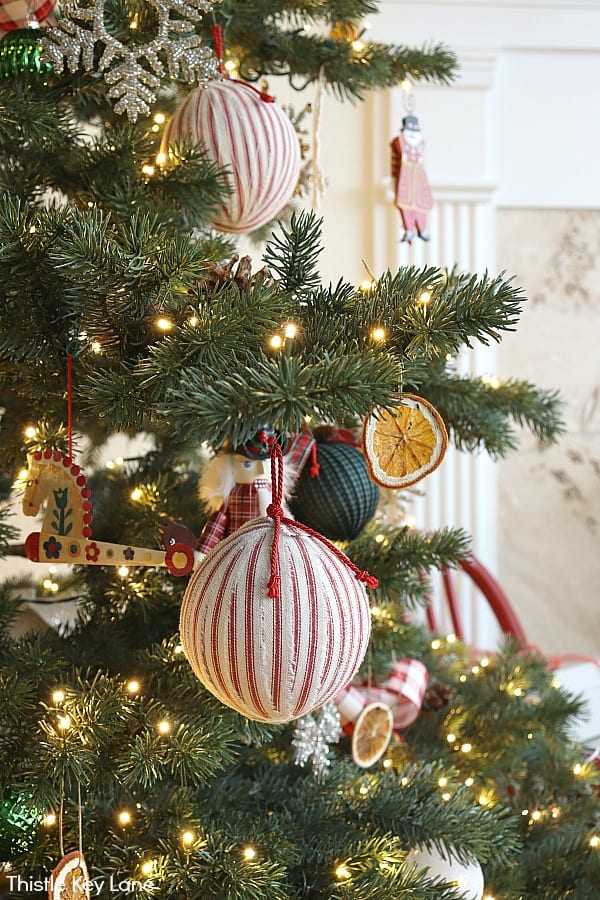 Ticking stripe ornaments hanging on the tree. Christmas In The Kitchen And Family Room.