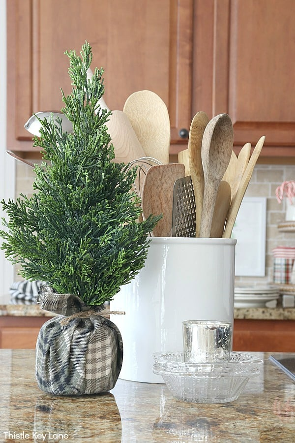 Faux cedar tree with plaid wrapped base and utensils in a crock.