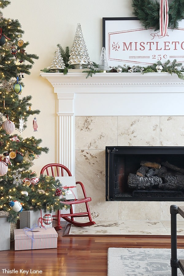 Christmas mantel with mercury glass, greenery, mistletoe sign and fireplace. Christmas In The Kitchen And Family Room.