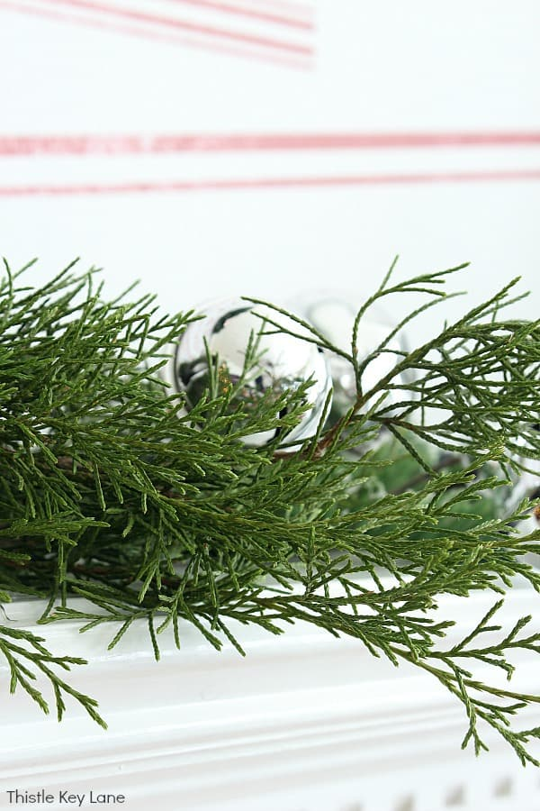 Cedar clipping and a shiny jingle bell on the mantel.