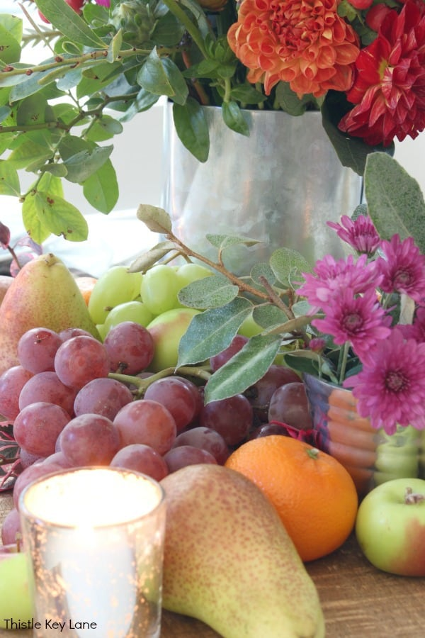 Arrangement of grapes, pears, oranges and flowers on a bread board.
