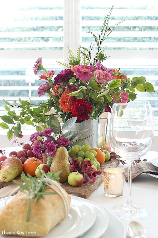 Centerpiece of flowers surrounded by fruit on a bread board.