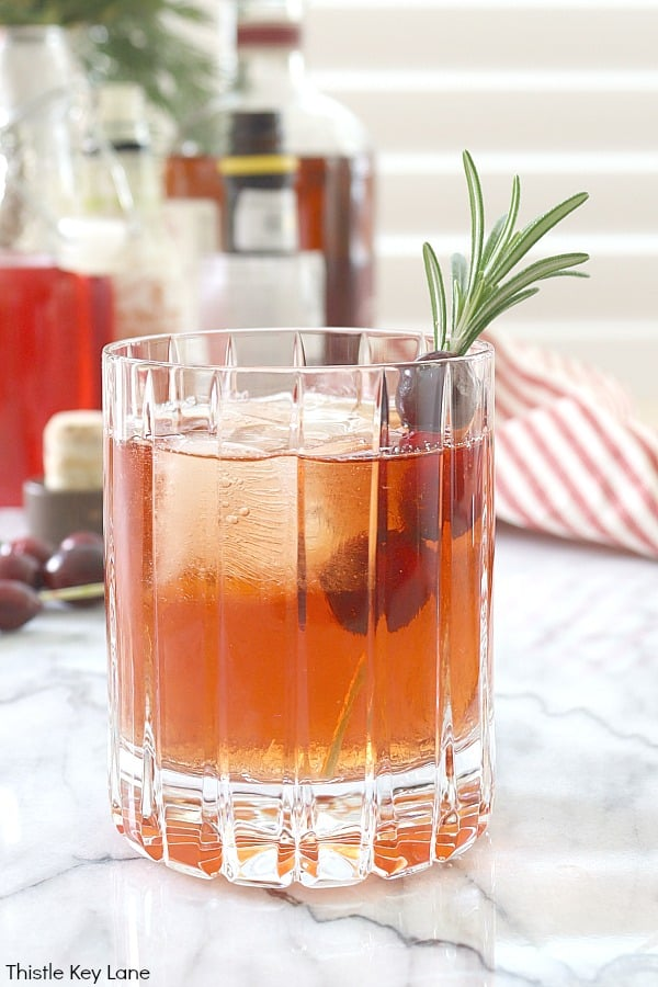 Cocktail with rosemary cranberry garnish. Cranberry Old Fashioned Cocktail Recipe.