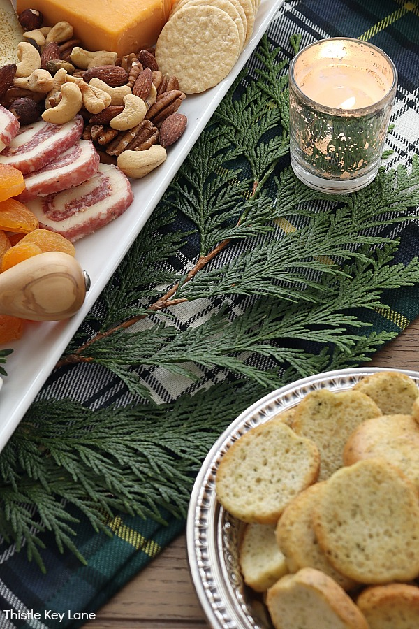 Charcuterie tray on top of cedar clippings. Evergreen Christmas Centerpiece And Tablescape.