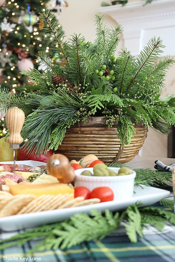Holiday table with evergreen centerpiece and appetizer tray. Evergreen Christmas Centerpiece And Tablescape.