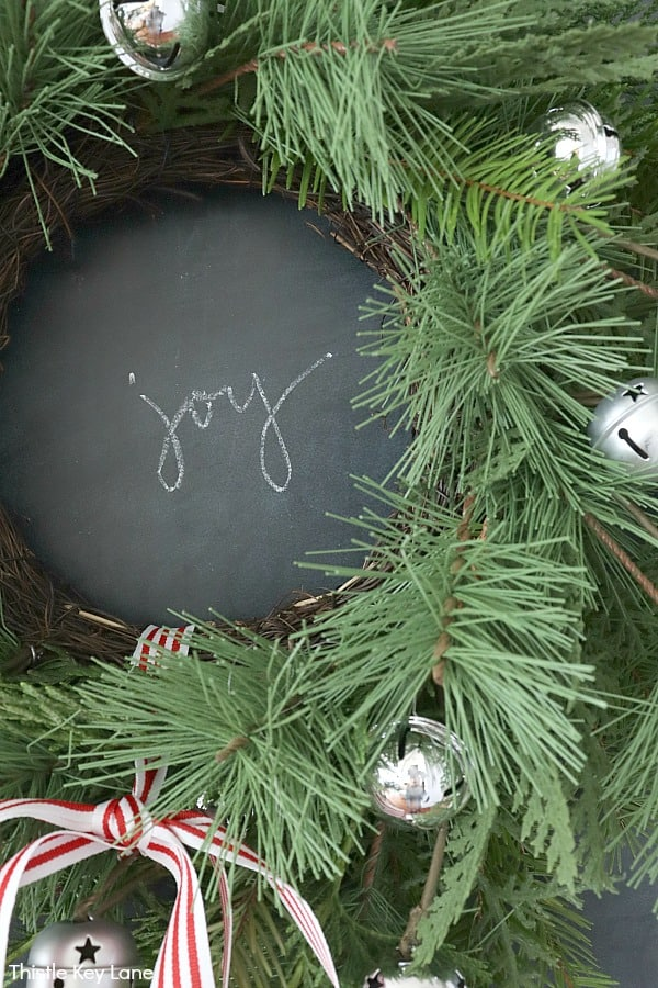 Joy written on a chalkboard framed by a pine wreath. How To Update A Wreath With Greenery.