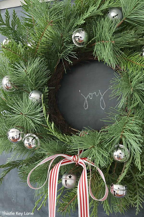 Green wreath with jingle bells on chalkboard. How To Update A Wreath With Greenery.
