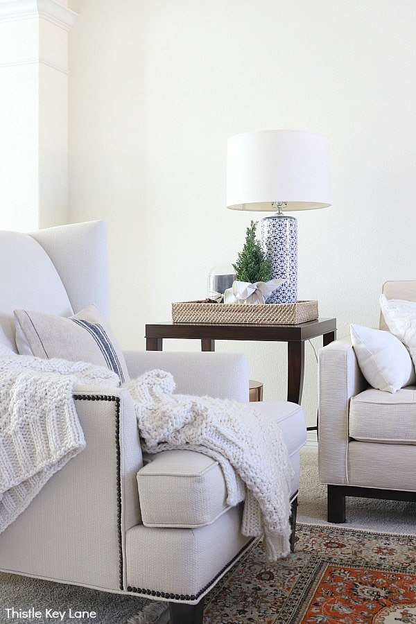 White wing back chair with knit throw. Blue and white lamp and faux tree on table tray.