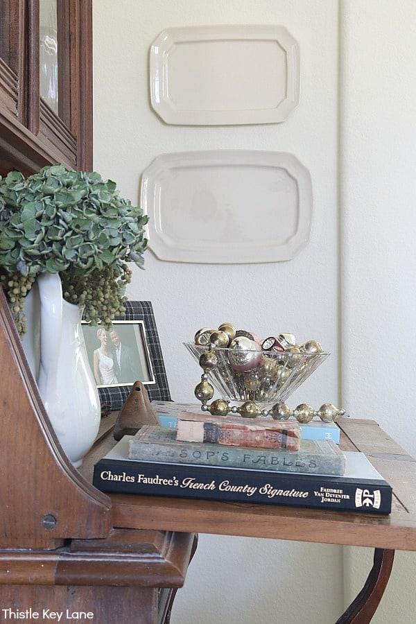 Books and a bowl of Christmas ornaments on a secretary desk. White Bottle Brush Tree Vignette.