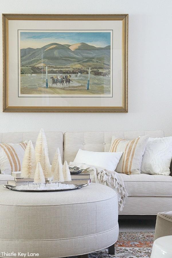 Neutral color ottoman and sofa in cream tones. White Bottle Brush Tree Vignette.